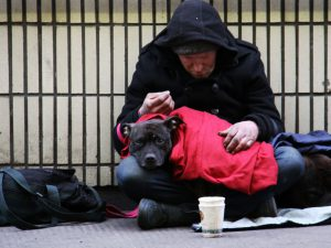 A homeless man and his dog sitting on a footpath