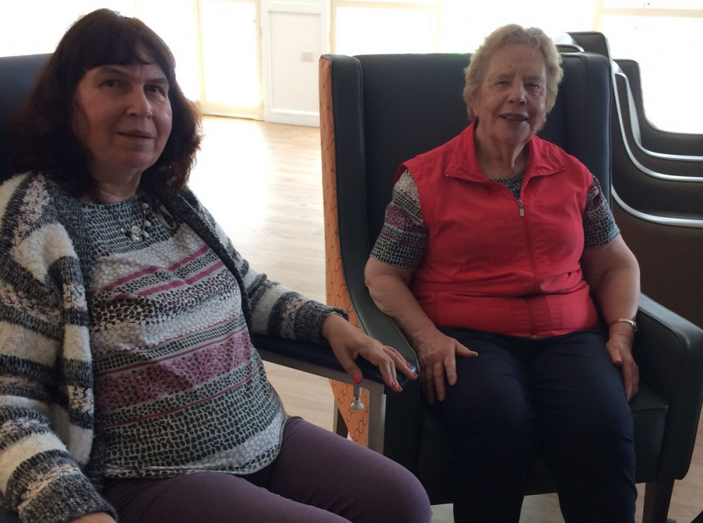 Resident and carer sitting in chairs smiling