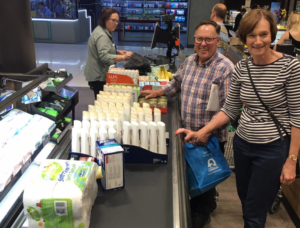 Two volunteers standing at Woolies check out with lots of goods