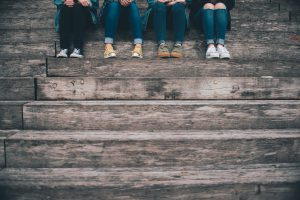 Teenagers sitting on steps, only their legs and feet are shown