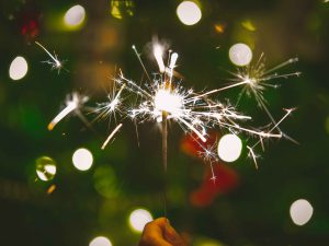 A sparkler in front of Christmas backdrop