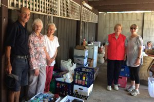 Volunteers standing amongst all the donations