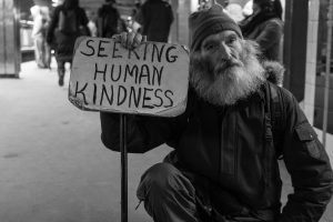 Homeless man holding a sign that says 'Seeking human kindness'